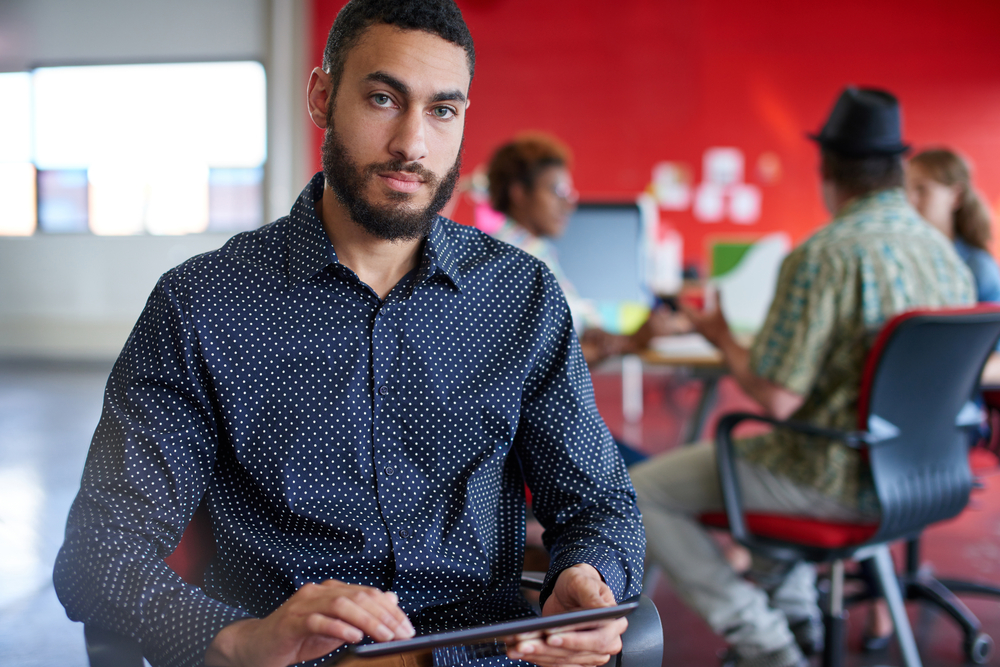 Confident male designer working on a digital tablet in red creative office space-1