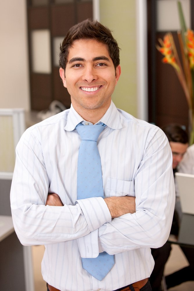 Handsome business man in an office smiling-1