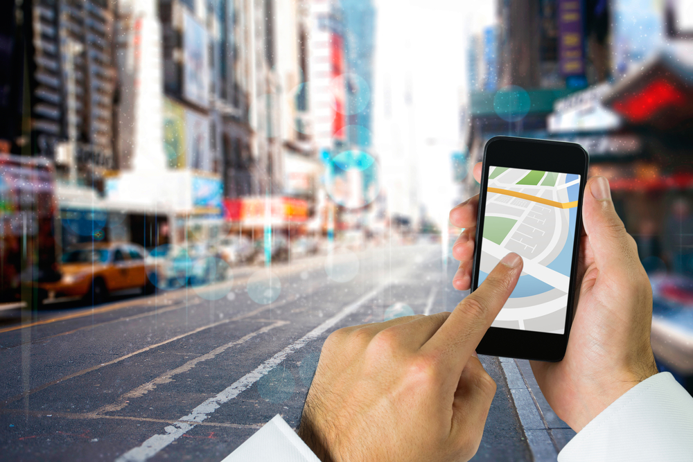 Man using map app on phone against blurry new york street