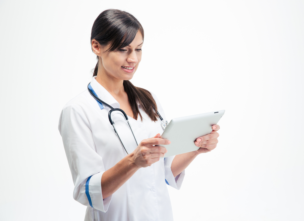 Smiling medical doctor using tablet computer isolated on a white background