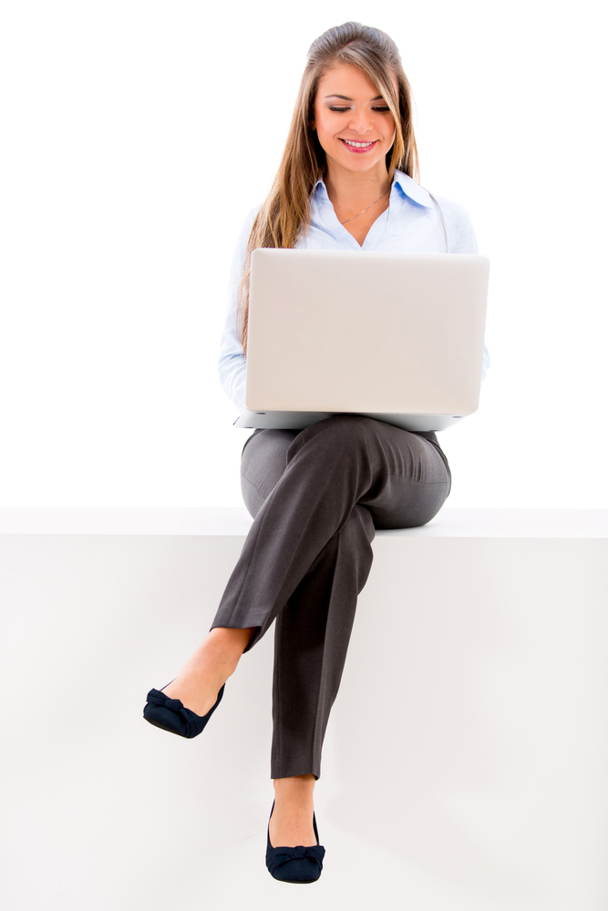 Beautiful businesswoman sitting with a laptop on her legs